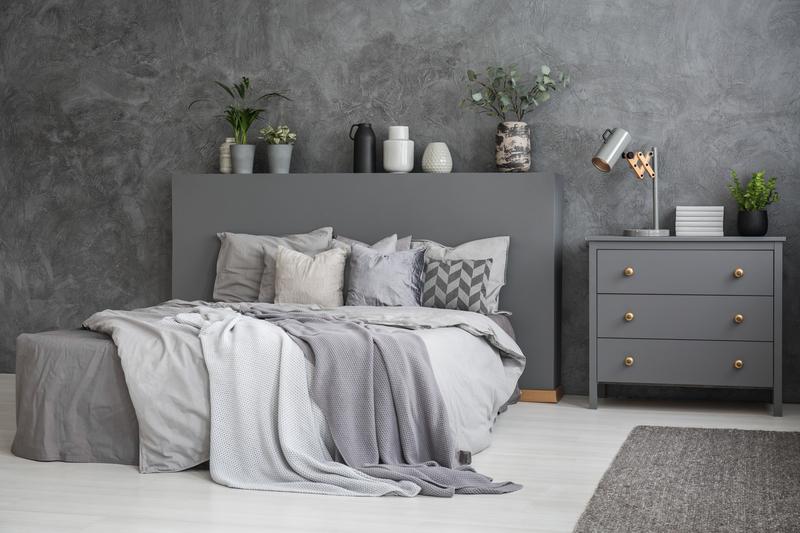 Je slaapkamer dient in de eerste plaats om tot rust te komen en te slapen. En in deze hectische wereld hebben we vast en zeker rust nodig. Misschien daarom dat de kleuren in de slaapkamer rustig en eenvoudig worden. Grijs is dé kleur voor de slaapkamer. Verschillende grijstinten brengen een levendige look zonder druk of overdadig te zijn. Maar hoe pak je het aan om je slaapkamer volledig of gedeeltelijk in grijstinten in te richten? Wij geven hier enkele tips om je te inspireren. Contrast creëren? Als je ervoor kiest om volledig binnen de grijstinten te blijven voor je slaapkamer, dan is het even opletten. Bepaal eerst of je contrasten wilt creëren of niet. Bekijk goed welke vlakken aan elkaar grenzen en kies in functie daarvan je tint grijs. Een donkergrijs bed op een lichtgrijze vloer geeft contrast. Een bijna-wit-grijs bed tegen een donkergrijze muur geeft contrast. Een donkergrijs dekbedovertrek op een lichtgrijs bed creëer contrast. Hou in het achterhoofd dat je bij grijstinten veel sneller contrasten krijgt dan wanneer je voor verschillende kleuren kiest. Grijs is een vrij harde kleur waardoor het contrast veel beter opvalt. Of geen contract? Wil je te grote contrasten vermijden? Bouw dan in horizontale richting (tussen vloer en plafond) of in verticale richting (van de ene naar de andere muur) je grijstinten op. In verticale richting ga je bijvoorbeeld voor een middel-grijze vloer, lichtgrijze meubelen en muren, en een bijna-wit-grijs plafond. Je raamdecoratie komt dan in dezelfde kleur als je muren, je vloerkleedje in dezelfde kleur als je vloer en je dekbedovertrek in dezelfde kleur als je bed. Als je horizontaal gaat werken, betekent dit dat je bijvoorbeeld één muur in heel licht grijs schildert en de tegenoverliggende muur in donker grijs. De andere twee muren, je plafond en je vloer kies je middel-grijs. Je kunt dan bijvoorbeeld kiezen voor een bed met enkel een hoofdbord in donker grijs tegen een donker grijze muur. Je dekbedovertrek krijgt de kleur van